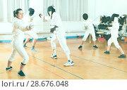 Купить «Young woman fencer practicing effective fencing techniques in training room», фото № 28676048, снято 30 мая 2018 г. (c) Яков Филимонов / Фотобанк Лори