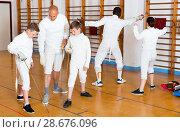 Купить «Focused boys fencers attentively listening to professional fencing coach in gym», фото № 28676096, снято 30 мая 2018 г. (c) Яков Филимонов / Фотобанк Лори