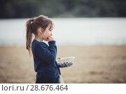 Купить «Девочка на улице есть голубику из стеклянной миски», фото № 28676464, снято 24 мая 2018 г. (c) Julia Shepeleva / Фотобанк Лори