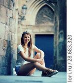 Купить «Young woman sitting near old stone wall», фото № 28683320, снято 15 августа 2017 г. (c) Яков Филимонов / Фотобанк Лори