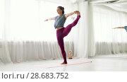 Купить «woman doing yoga hand-to-big-toe pose at studio», видеоролик № 28683752, снято 28 июня 2018 г. (c) Syda Productions / Фотобанк Лори