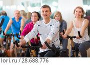 Купить «Man on fitness cycle training», фото № 28688776, снято 15 декабря 2018 г. (c) Яков Филимонов / Фотобанк Лори