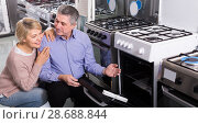 Купить «interested mature couple chooses in shop of household appliances gas stove with oven», фото № 28688844, снято 18 июля 2018 г. (c) Яков Филимонов / Фотобанк Лори