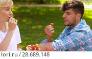 Купить «happy friends eating strawberries at summer picnic», видеоролик № 28689148, снято 26 июня 2018 г. (c) Syda Productions / Фотобанк Лори