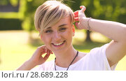 Купить «portrait of happy young woman in summer park», видеоролик № 28689228, снято 26 июня 2018 г. (c) Syda Productions / Фотобанк Лори