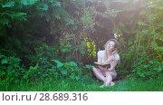 Купить «Attractive woman hipster sitting under a bushes and reading a book at sunset», видеоролик № 28689316, снято 17 июля 2018 г. (c) Константин Шишкин / Фотобанк Лори