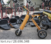 Купить «Оранжевый электрический велосипед с ключом в замке зажигания на площадке проката», фото № 28696348, снято 24 июня 2018 г. (c) Наталья Николаева / Фотобанк Лори