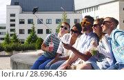 Купить «friends taking picture by on selfie stick in city», видеоролик № 28696436, снято 27 июня 2018 г. (c) Syda Productions / Фотобанк Лори