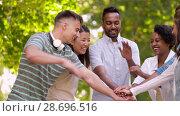 Купить «happy friends stacking hands in summer park», видеоролик № 28696516, снято 25 июня 2018 г. (c) Syda Productions / Фотобанк Лори