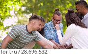 Купить «happy friends stacking hands in summer park», видеоролик № 28696532, снято 25 июня 2018 г. (c) Syda Productions / Фотобанк Лори