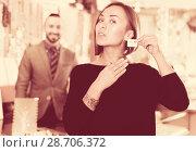 Купить «Buyer woman choosing earrings in jewelry store», фото № 28706372, снято 16 октября 2017 г. (c) Яков Филимонов / Фотобанк Лори
