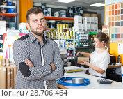 Купить «Male with tools and woman seller at cash desk», фото № 28706464, снято 17 мая 2018 г. (c) Яков Филимонов / Фотобанк Лори