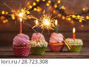 Купить «cupcake with sparkler on old wooden background», фото № 28723308, снято 14 декабря 2017 г. (c) Майя Крученкова / Фотобанк Лори