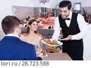 Купить «Positive waiter serving seafood meals to guests», фото № 28723588, снято 26 января 2018 г. (c) Яков Филимонов / Фотобанк Лори