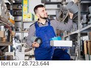 Купить «Male worker choosing drain pipe detail», фото № 28723644, снято 15 марта 2017 г. (c) Яков Филимонов / Фотобанк Лори