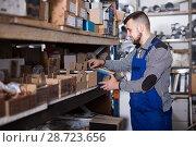 Купить «Worker sorts small parts for repair», фото № 28723656, снято 15 марта 2017 г. (c) Яков Филимонов / Фотобанк Лори