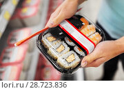 Купить «hands with sushi pack at grocery or supermarket», фото № 28723836, снято 2 ноября 2016 г. (c) Syda Productions / Фотобанк Лори