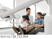 Купить «dentist showing tablet pc to kid patient at clinic», фото № 28723964, снято 22 апреля 2018 г. (c) Syda Productions / Фотобанк Лори