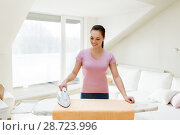 Купить «woman or housewife ironing towel by iron at home», фото № 28723996, снято 29 апреля 2018 г. (c) Syda Productions / Фотобанк Лори