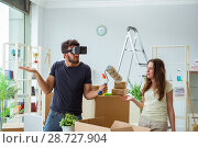 Купить «Young family with virtual glasses unpacking at new house with bo», фото № 28727904, снято 8 июля 2017 г. (c) Elnur / Фотобанк Лори