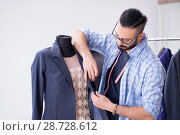 Купить «Male tailor working in the workshop on new designs», фото № 28728612, снято 12 апреля 2018 г. (c) Elnur / Фотобанк Лори