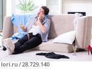 Купить «Man with mess at home after house party», фото № 28729140, снято 14 марта 2018 г. (c) Elnur / Фотобанк Лори