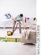 Купить «Young man husband doing vacuuming at home», фото № 28729816, снято 1 мая 2018 г. (c) Elnur / Фотобанк Лори