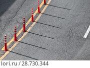 Купить «Dividing line and red plastic warning poles», фото № 28730344, снято 17 марта 2018 г. (c) EugeneSergeev / Фотобанк Лори
