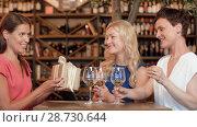 Купить «women giving present to friend at wine bar», видеоролик № 28730644, снято 6 июля 2018 г. (c) Syda Productions / Фотобанк Лори