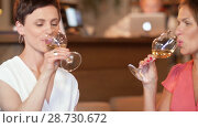 Купить «happy women drinking wine at bar or restaurant», видеоролик № 28730672, снято 4 июля 2018 г. (c) Syda Productions / Фотобанк Лори