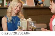 Купить «women giving present to friend at wine bar», видеоролик № 28730684, снято 4 июля 2018 г. (c) Syda Productions / Фотобанк Лори