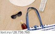 Купить «beach bag, sunscreen, sunglasses and hat on sand», видеоролик № 28730760, снято 5 июля 2018 г. (c) Syda Productions / Фотобанк Лори