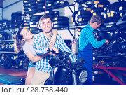 Купить «Cheerful couple sitting on motorcycle at service point», фото № 28738440, снято 12 декабря 2018 г. (c) Яков Филимонов / Фотобанк Лори