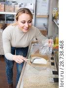 Купить «Woman picking cereals in organic store», фото № 28738468, снято 19 апреля 2019 г. (c) Яков Филимонов / Фотобанк Лори