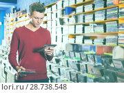 Купить «guy looking on box of DVD movie», фото № 28738548, снято 15 февраля 2018 г. (c) Яков Филимонов / Фотобанк Лори