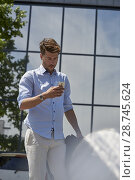 Купить «Portrait of Youtuber Axel Sprenger using smartphone in front of glass architecture reflecting tree, wearing business clothes. Contrast city life and nature. In Germany, Bavaria.», фото № 28745624, снято 7 мая 2018 г. (c) age Fotostock / Фотобанк Лори