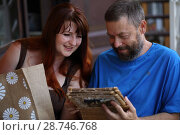 Купить «Счастливые мужчина и женщина смотрят фотоальбом», фото № 28746768, снято 9 июня 2018 г. (c) Марина Володько / Фотобанк Лори