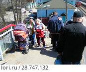 Купить «Женщины с коляской поднимаются по лестнице надземного пешеходного перехода станции Волоколамск. Город Волоколамск. Московская область», эксклюзивное фото № 28747132, снято 6 мая 2015 г. (c) lana1501 / Фотобанк Лори