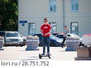 Купить «Tyumen, Russia, on July 15, 2018: the teenage boy rides a giroskuter in the summer on the square», фото № 28751752, снято 15 июля 2018 г. (c) Землянникова Вероника / Фотобанк Лори