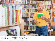 Купить «Focused senior man choosing book at bookshelves in bookshop», фото № 28752144, снято 11 июня 2018 г. (c) Яков Филимонов / Фотобанк Лори