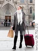 Купить «Cheerful young girl in scarf with baggage», фото № 28752272, снято 11 ноября 2017 г. (c) Яков Филимонов / Фотобанк Лори