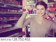 Купить «Glad female searching for reliable nail polish», фото № 28752432, снято 21 февраля 2017 г. (c) Яков Филимонов / Фотобанк Лори