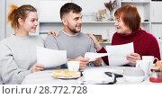 Купить «Smiling family discussing documents», фото № 28772728, снято 27 ноября 2017 г. (c) Яков Филимонов / Фотобанк Лори