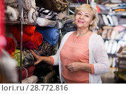 Купить «Female standing among shelf shelf in the textile shop», фото № 28772816, снято 29 ноября 2017 г. (c) Яков Филимонов / Фотобанк Лори