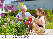 Купить «grandmother and girl planting flowers at garden», фото № 28773260, снято 3 июня 2018 г. (c) Syda Productions / Фотобанк Лори