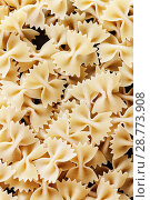 Купить «Italian Farfalle Pasta raw food background or texture close up», фото № 28773908, снято 25 апреля 2018 г. (c) Tetiana Chugunova / Фотобанк Лори