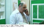 Купить «Senior pharmacist talking on mobile phone while checking prescription in pharmacy», видеоролик № 28779216, снято 6 апреля 2017 г. (c) Vasily Alexandrovich Gronskiy / Фотобанк Лори
