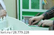 Купить «Male customer buy tablet pay with dollars cash at pharmacy counter», видеоролик № 28779228, снято 6 апреля 2017 г. (c) Vasily Alexandrovich Gronskiy / Фотобанк Лори
