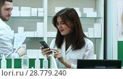 Купить «Young female pharmacist texting messages using mobile phone, smiling and talking to her male colleauge», видеоролик № 28779240, снято 6 апреля 2017 г. (c) Vasily Alexandrovich Gronskiy / Фотобанк Лори