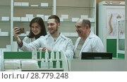 Купить «Cheerful team of pharmacist and interns take selfie via smartphone at workplace», видеоролик № 28779248, снято 6 апреля 2017 г. (c) Vasily Alexandrovich Gronskiy / Фотобанк Лори